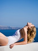 Woman in bathing suit reclining outdoors