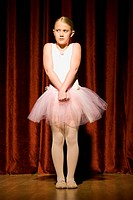Ballerina girl with hands clasped nervously