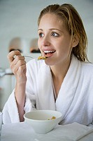 Woman in bathrobe eating cereal