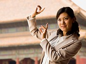 Businesswoman doing tai chi outdoors smiling