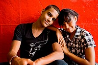 Teen boy and girl in front of red wall, portrait