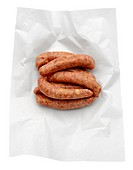 Raw uncooked sausages in grease paper