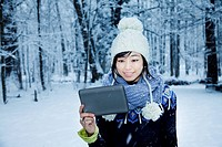 woman reading on tablet computer, snow falling