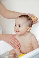 mum washing baby´s head in bathtub