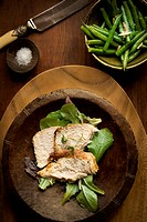 Roasted chicken breast sliced on bed of greens
