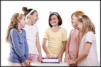 five girls around a birthday cake