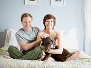 couple on their bed with their dog