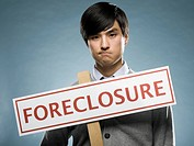 man holding a foreclosure sign