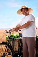Farmer walking bike with vegetable