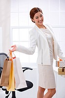 Young business lady holding shopping bags