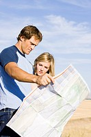 couple looking at a map on the side of the road