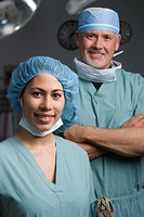 Portrait of a male doctor standing behind a female doctor and smiling