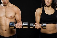 Mid adult man and a young woman exercising with dumbbells