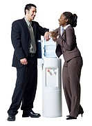 Businessman and a businesswoman standing beside a water cooler