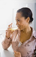 Close_up of a young woman enjoying a glass of white wine