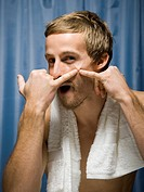 Portrait of a young man squeezing a zit