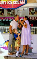 Couple with pregnant woman and boy eating ice creams