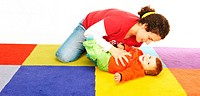 Mother Play with her ten months old baby girl on a colored carpet