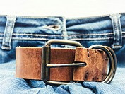 Jeans with brown leather belt in foreground