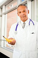 A middle aged doctor holding a banana inside.