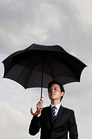 Man holding an umbrella looking worried.