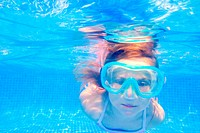 blond child girl underwater swimming in pool
