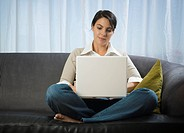 Mid adult woman sitting on a couch working on a laptop