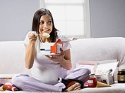 Pregnant woman sitting on a couch and eating ice_cream