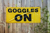 Goggles on sign on wooden fence at paintball field, Oregon