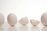 A row of eggs with one broken egg