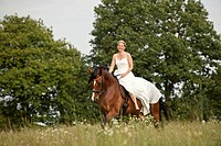 Woman wearing a wedding dress trotting across a meadow on a Hanoverian horse