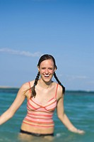 Portrait of a teenage girl standing in water and smiling