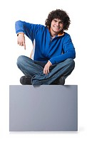 Portrait of a teenage boy sitting on a blank sign and pointing