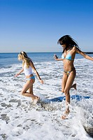 Profile of two young women running in the water on the beach