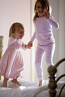 Two girls jumping on the bed
