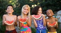 Close_up of children holding watermelons and smiling