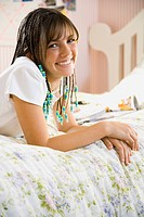 Girl with braids lying down on bed smiling