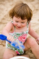 Girl on sandy beach with toy shovel