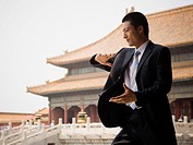 Businessman doing tai chi outdoors smiling