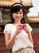 Teenage girl listening to mp3 player and smiling