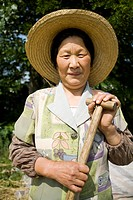 Woman with straw hat and shovel standing outdoors smiling