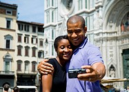 Couple hugging and taking self portrait with camera