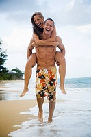 Man giving woman piggyback ride on beach