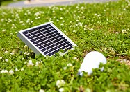 Solar panel and a LED bulb in grassland
