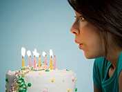 Profile of woman blowing out candles on birthday cake