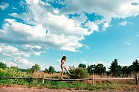 Teenage girl balancing on wooden fence