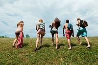 Five friends walking in field, rear view