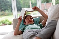 Boy lying on sofa and reading a book
