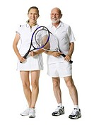 Portrait of a senior couple standing with tennis rackets