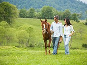 man and a woman walking with a horse